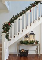 White-painted wooden staircase decorated with fir branches and Christmas decorations above lanterns on console table with curved legs