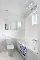 White designer bathroom; toilet with cistern against tiled wall, bathtub with marble surround and marble floor