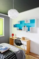 Wall-mounted shelves with pale blue back wall above simple console table in bedroom