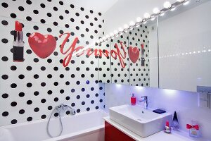 Writing, heart and lipstick on bathroom wall with black polka-dots and mirrored wall with row of spotlight above sink