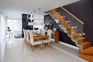 Dining area with pale, upholstered chairs below pendant lamps next to wooden staircase with glass balustrade and black wall with recessed spotlights