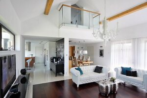 Elegant, white leather sofa set in lounge area below balcony in open-plan interior