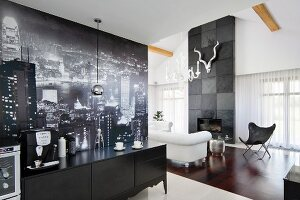 Black, postmodern sideboard against black and white photo mural on wall; sofa and Butterfly Chair in lounge area in background