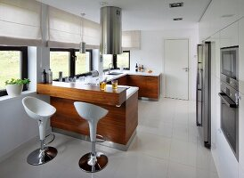 Designer bar stools at counter under cylindrical, stainless steel extractor hood in open-plan kitchen