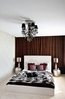 Double bed with tall headboard and fur blanket and Oriental side tables and table lamps in front of brown curtain