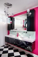 Black washstand with twin sinks below black, wall-mounted cabinet and mirror on hot-pink wall