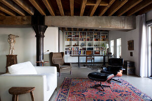 White, modern couch and classic Eames Lounge Chair on Oriental rug in front of study area with bookcase