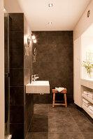 Designer bathroom with grey tiles on walls and floor, minimalist fittings and custom shelving below window in niche