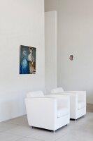 White, designer armchairs below picture on wall in minimalist interior