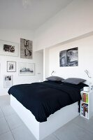 Double bed with white frame and black bedspread in modern bedroom