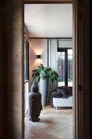 View through open door; head of Buddha, herringbone parquet floor and tall, grey planter in corner