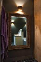 Designer washstand reflected in gilt-framed mirror, purple towel and wooden cupboard in atmospheric lighting