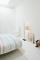 Bed with patterned bedspread, standard lamp and fitted wardrobes in minimalist, white bedroom