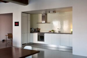 View from dining area into open-plan, white kitchen with illuminated niche