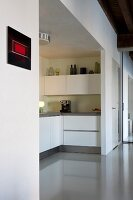 White, U-shaped, fitted kitchen in niche and glossy, grey resin floor