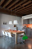 Stainless steel kitchen counter with orange wall tiles, rustic wood-beamed ceiling and wooden table with white designer chairs in loft apartment