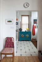 Chair next to open doorway with view of blue-painted cabinet below window in foyer with tiled floor