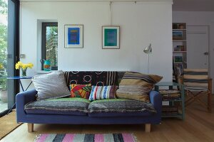 Patterned blanket and various scatter cushions on blue sofa against wall in contemporary interior