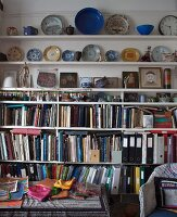 Colourful fabrics on table below shelves holding books and ornamental plates