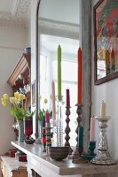 Coloured candles in various silver candlesticks in front of mirror on mantelpiece