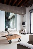 Coffee table on castors in front of pale ottomans in lounge area of loft apartment