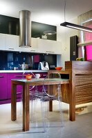 Wooden counter with extendable table and ghost chair; fitted kitchen with bold accents of colour in background