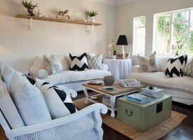 Vintage-style living room with scatter cushions on white sofas, wicker armchair, coffee table and stacked magazines on wooden trunk