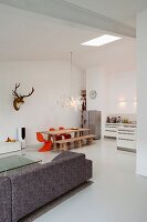 Modern, minimalist loft apartment - view from lounge area to dining area with hunting trophy and Zettel'z lamp by Ingo Maurer in open-plan kitchen