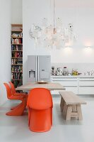 Dining area with orange classic chairs below Zettel'z lamp by Ingo Maurer in open-plan kitchen