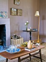Glasses in white and blue dish and jug on coffee table in front of fireplace; retro standard lamp next to bistro table in background