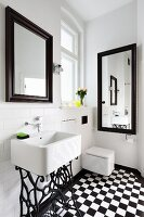 Sink on vintage sewing machine frame in bathroom with black and white chequered floor