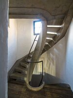 Concrete spiral staircase in renovated stairwell with patterns of light and shade