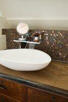 Amorphous basin on custom, wood-veneer washstand with mosaic-tiled splashback and shaving equipment on shelf