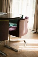 Upholstered cantilever chairs around table on parquet floor