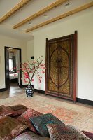 Elegant, silk cushions on couch, antique Moroccan door and floor vase on Persian rug