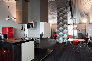 Modern kitchen area with extractor hood above free-standing counter and dining area in renovated loft apartment