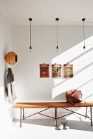 Pattern of light and shade in hallway with bulb pendant lamps above wooden bench, artworks on wall and coat hooks to one side with original storage bin