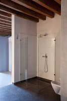 Minimalist, easy-access shower with glass screens in loft apartment with wood-beamed ceiling