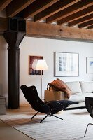 Retro-style, black armchair with footrest and standard lamp next to sofa in loft-apartment with industrial character
