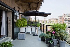 Planters and open parasol above seating area on terrace of penthouse apartment with view across city
