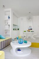 Colourful glass containers on round, white coffee table; white fitted kitchen with dining table in background