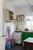 Vintage gas cooker against tiled wall next to counter with green-painted base units below window in simple kitchen
