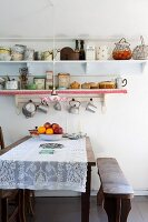 Lace tablecloth on dining table, antique bench and retro crockery on wall-mounted shelves