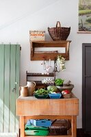 Fresh vegetables and kitchen utensils on rustic wooden kitchen table below wooden shelf on wall