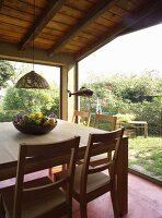 Pale wooden table and chairs in room with glass walls and view of garden