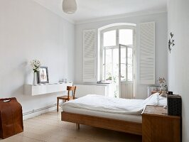 Bed with simple wooden frame, wooden bedside cabinet, white floating sideboard and window with white, interior shutters in bedroom
