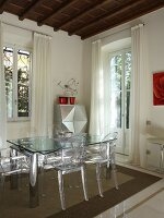 Dining set with glass table and postmodern Ghost chairs in period apartment with wooden ceiling