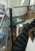 Winding, black metal staircase in modern interior with gallery