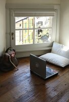 Laptop and comfortable cushions next to window on old wooden floor