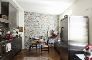 Kitchen with stainless steel fronts and fridge-freezer either side of dining set against brick wall